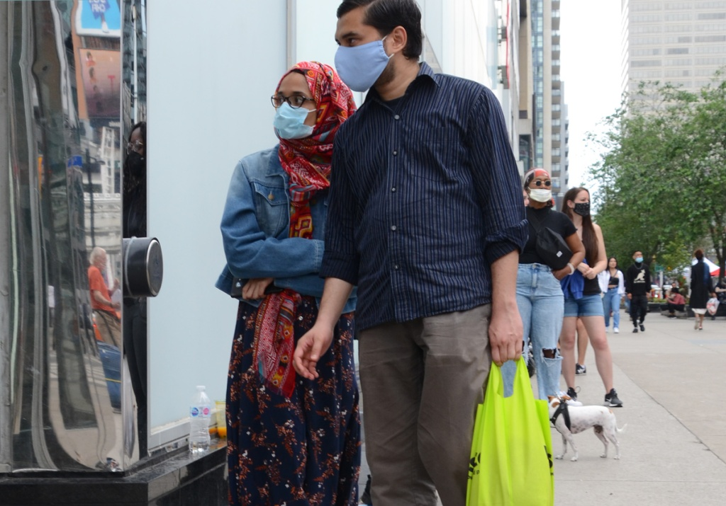 people waiting in line.  first woman has mask, glasses and a red head scarf. she's with a man carrying a yellow plastic grocery bag, other women in the line behind them, at Yonge and Dundas