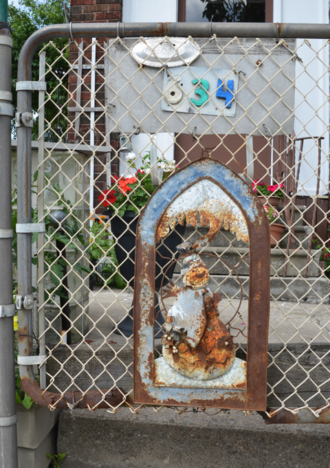 an old rusted metal decoration on a chainlink gate.  laughing snowman, front steps and flowers in planters in the background