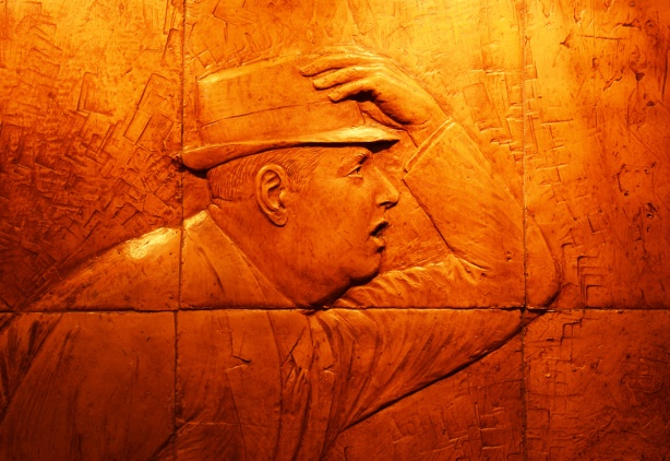 part of relief sculpture at Dundas subway station, a man holds on to his hat as he hurries along