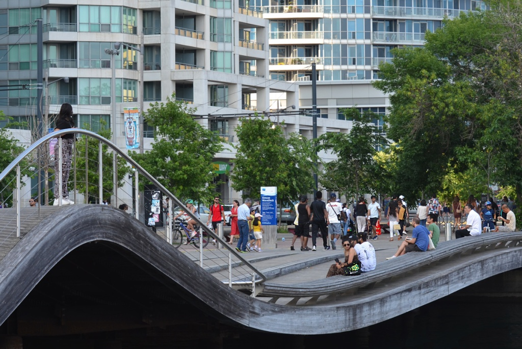 people sitting and walking on the Simcoe Wave Deck, Toronto waterfront, with condos behind