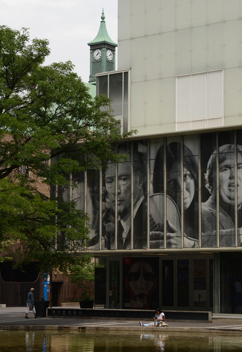 photographs of famous Canadians on the outer wall of Ryerson Image Center, with woman sitting on the concrete surrounding the reflecting pool by the entrance to R I C
