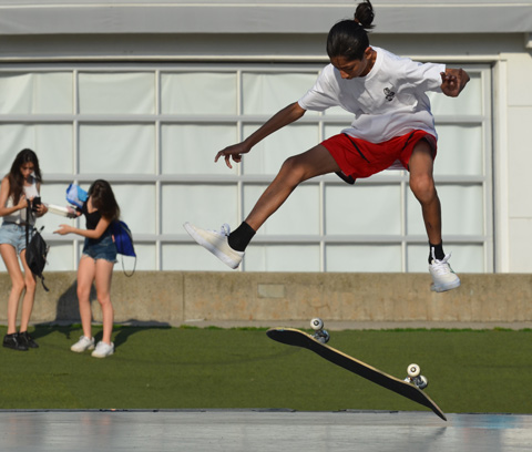 Young man in red shorts performing stunts on his skateboard