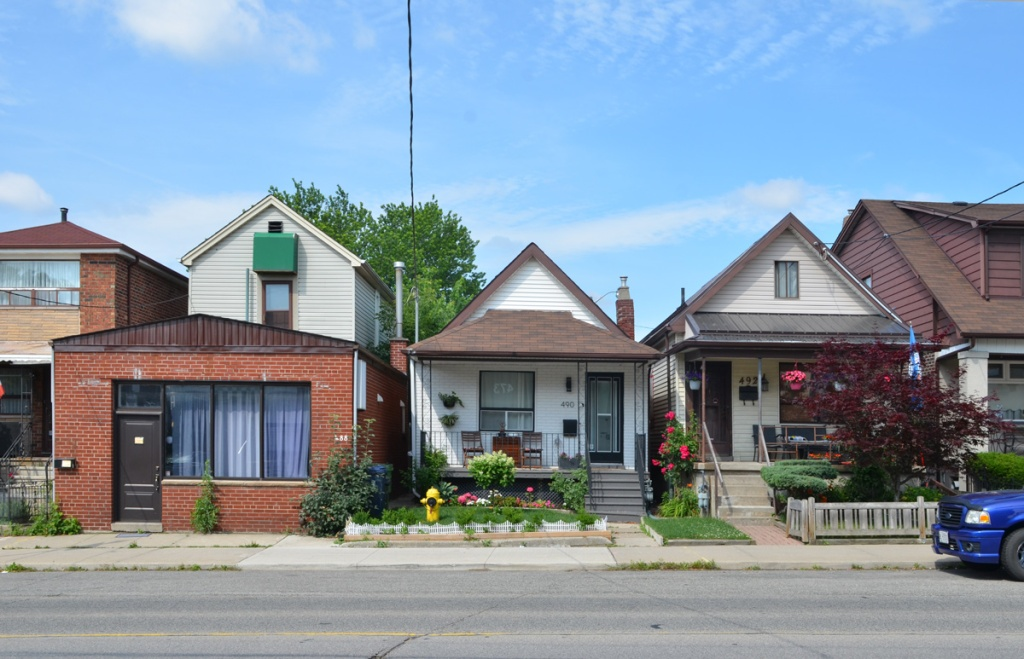 two small houses pus a couple of slightly larger houses on Oakwood, two have front porches with chairs on them, and well tended front lawns