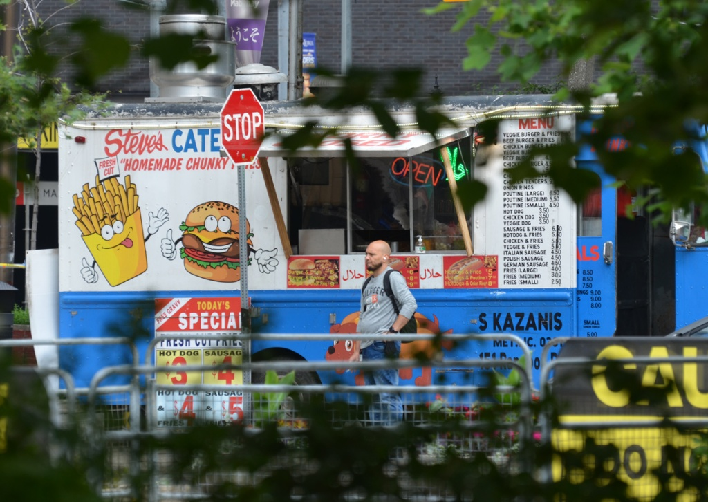a man waits for his order from a food truck Steve's catering with images of cartoon fries and hamburger on the side of the truck, S. Kazanis truck, menu also on side of truck, today's special hot dog three dollars and sausage four dollars