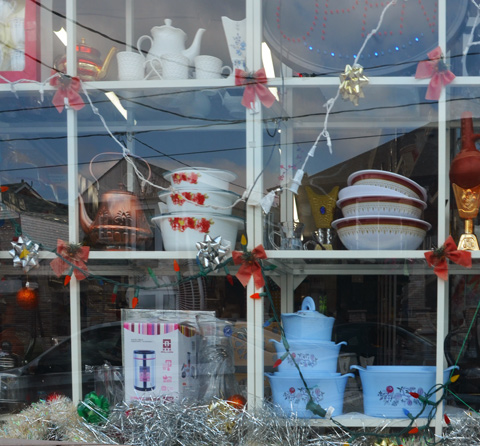 items for sale in displayed in store window that is still decorated for Christmas even though it is summer.  Bowls, tea pots, dishes