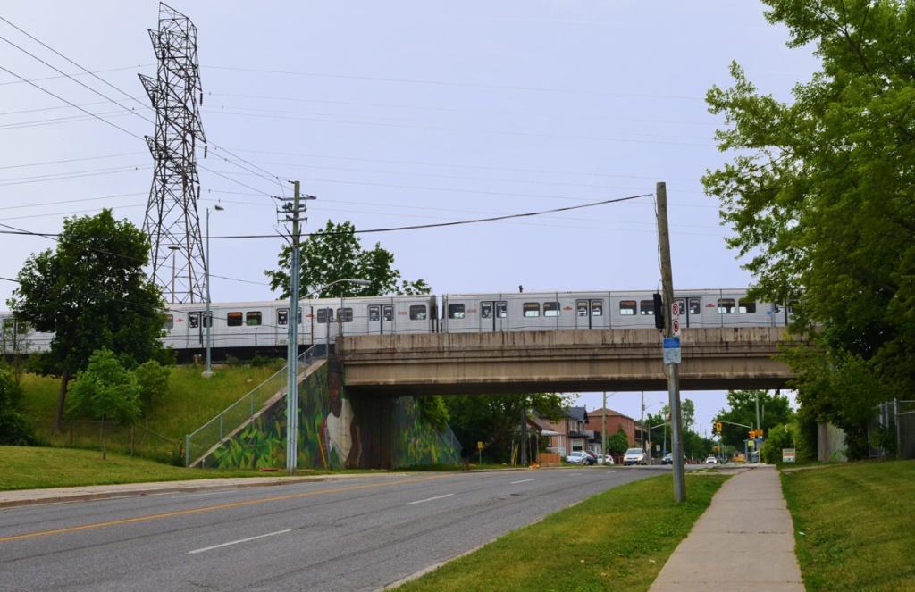 silver colour TTC subway crosses over bridge over Pharmacy Ave in Scarborough