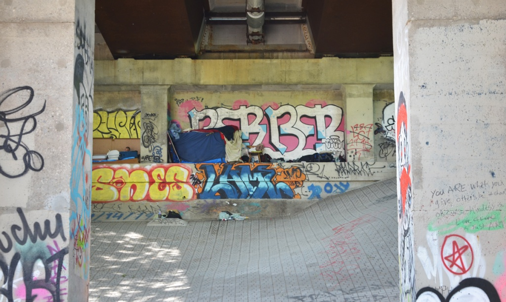 tent and belongings of a homeless man under a bridge surrounded by tags and other graffiti