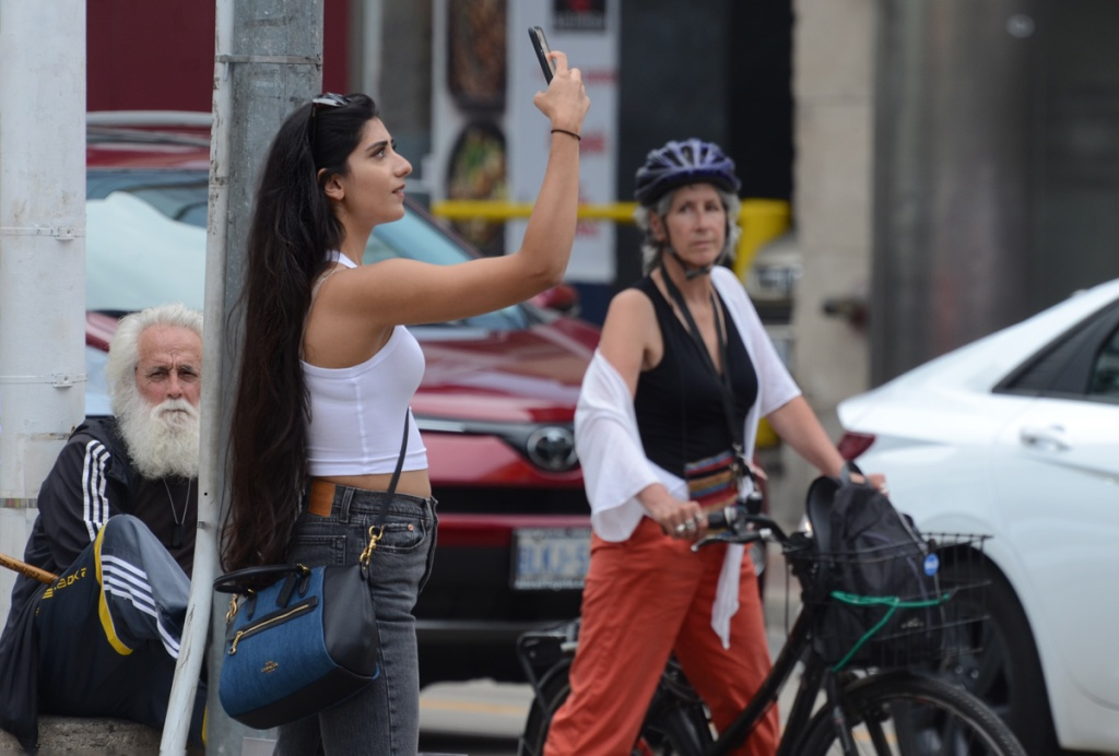 three people at Yonge and Dundas.  One is a woman standing with her bike waiting for the red light, second is a woman in cropped white tank top taking a selfie, and third an older man with white hair, white beard and white mustache.