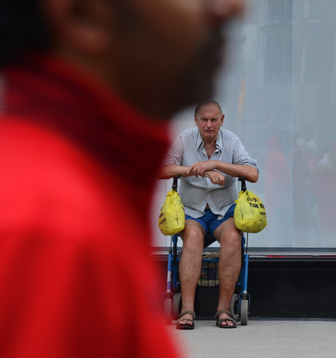 an older man in blue shorts and balding hair sits on a walker with a yellow grocery plastic bag on each handle.  out of focus close up of man in red top in the immediate foreground