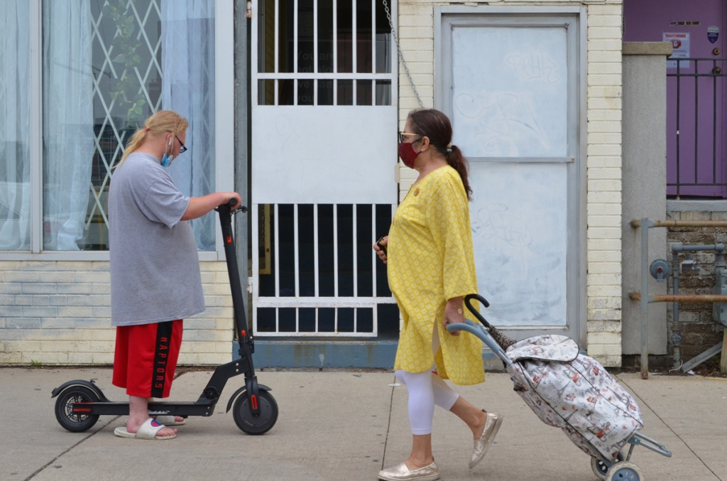 two people passing each other on a sidewalk, a man in red raptors shorts on a scooter and a woman with a long yellow top pulling a shopping buggy