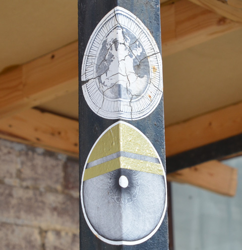 2 round paper paste up slaps on a pole.  The upper one shows a map of the world with the Atlantic Ocean in the center, the lower one is the round part of an eye