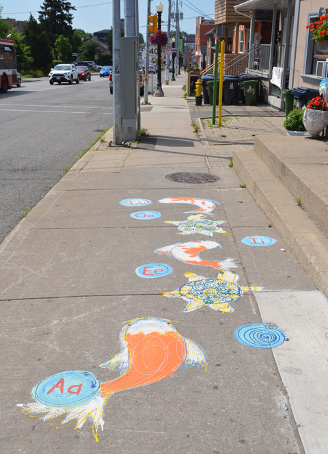 drawings and paintings on the sidewalk featuring vowels, A E I O and U