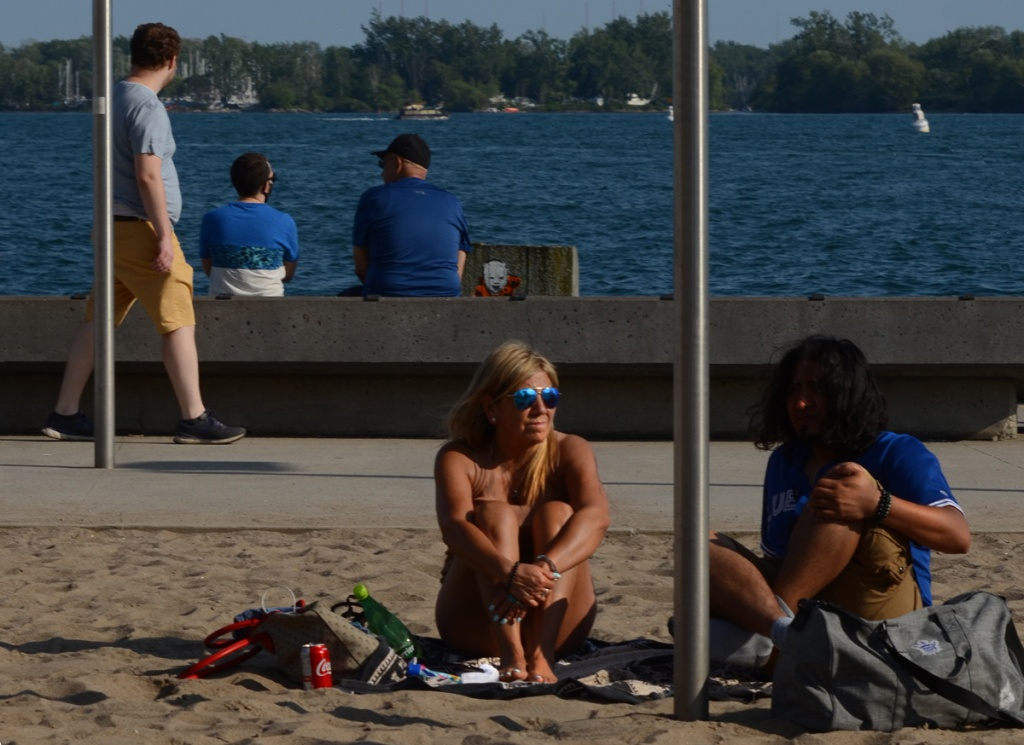 A couple sit on the sand on waterfront, under yellow umbrella, a man walks past behind them, also two men sitting on the edge of the lake,.