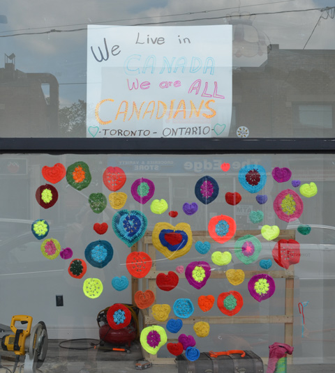 hand written sign in window that says We live in Canada We are all Canadians, Toronto Ontario, Below sign is a heart made of crocheted circles in different colours
