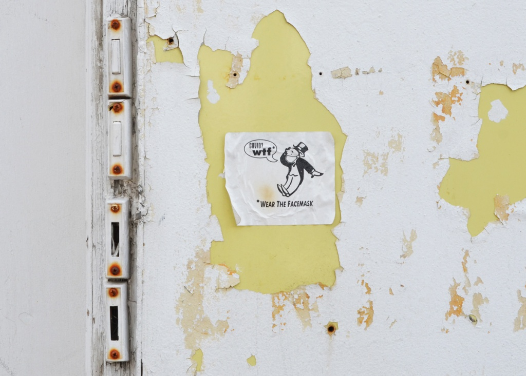 4 broken front door bell buzzers on a white peeling paint wall showing yellow paint below.  sticker on yellow with man from monopoly game saying covid? wtf*?  *wear the mask