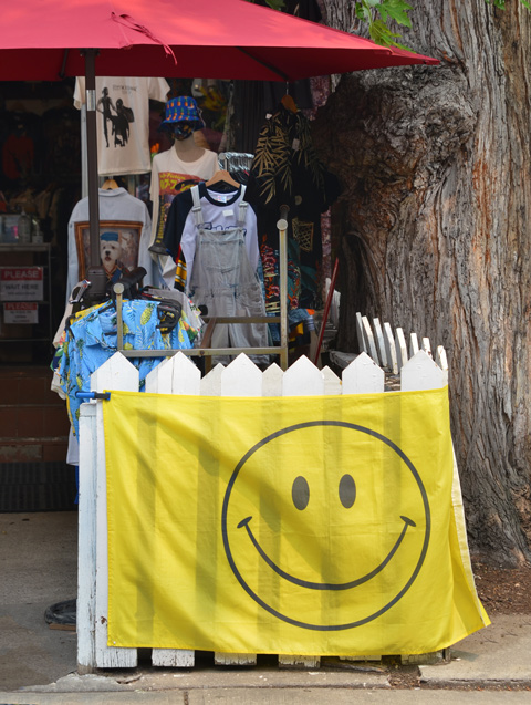 a large flag draped around a white picket fence, flag is yellow with a big happy face on it