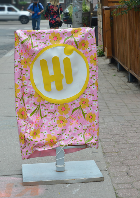 sign on sidewalk made with pink fabric covered with yellow and white flowers, a big white circle in the middle with hi written in large yellow letters