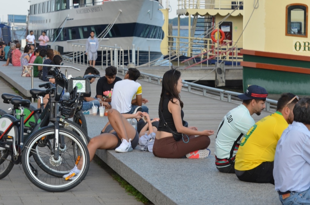 People sitting and lying on benches on waterfront, in front of the tour boats Northern Spirit and Obsession.  One woman is doing yoga pose.