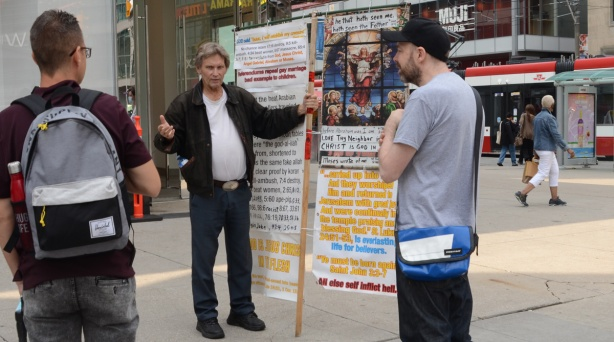 a man stands beside his Christian religious display at Yonge Dundas square while he talks to two men about Jesus