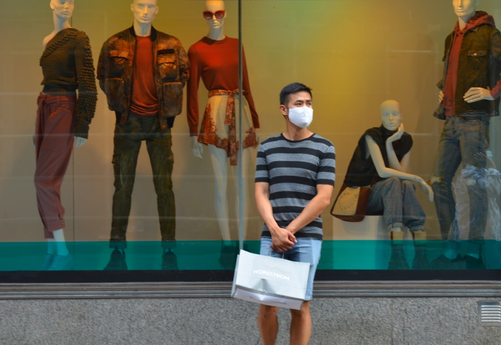 a young man with a mask and a Nordstroms shopping bag stands in front of the H B C windows with 5 mannequins modelling clothing