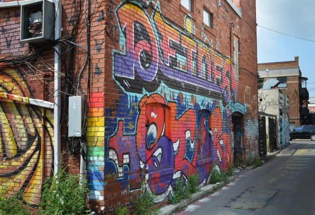 mural on a red brick building in a lane
