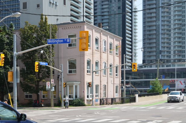 southeast corner of Bathurst and Wellington, pale pink three storey building on the corner, newer glass and steel condos behind
