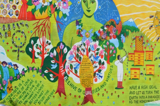 close up of part of the bee mural on the side wall of the bee shop. green woman, trees, bees, honeycomb, words, the beehive of qualities and virtues