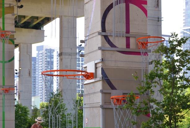 many different sizes of basketball hoops with chains mounted at different heights along the Bentway, part of art installation Playing in Public