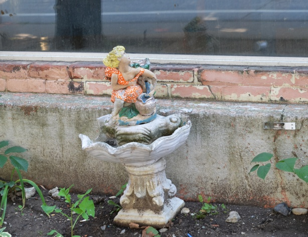 little blond doll with orange dress on top of a small stone birdbath shape outside a building, she looks to be looking in the window