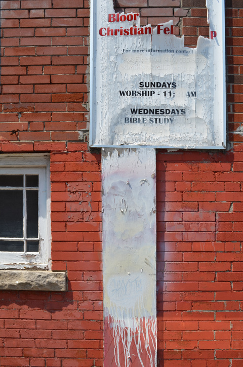 weathered sign beside Baptist church