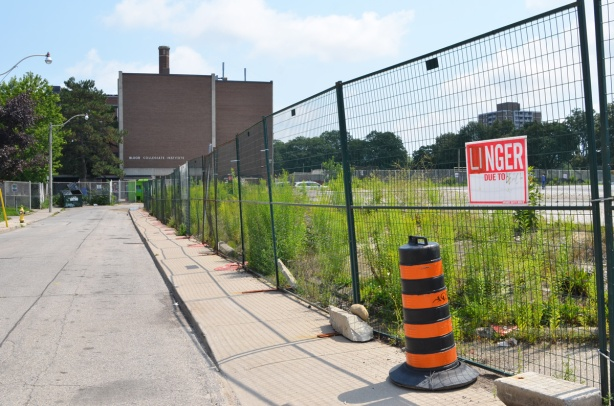 vacant lot with fence around it, Bloor Collegiate Institue in the background,