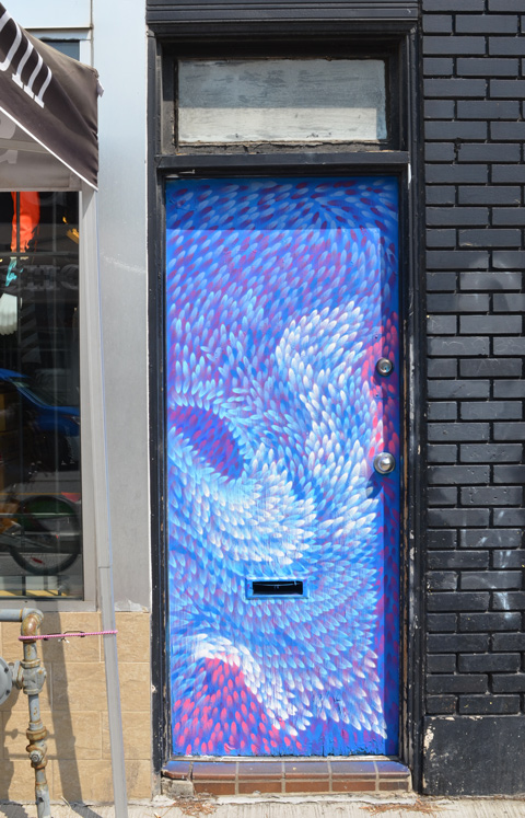 a door on Bloor Street painted in pink, blue, and white dabs