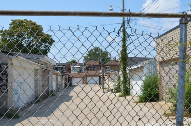 an alley with garages on both sides, behind chainlink fence