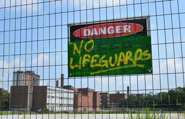 sign on fence around vacant lot that says danger no lifeguards, no water