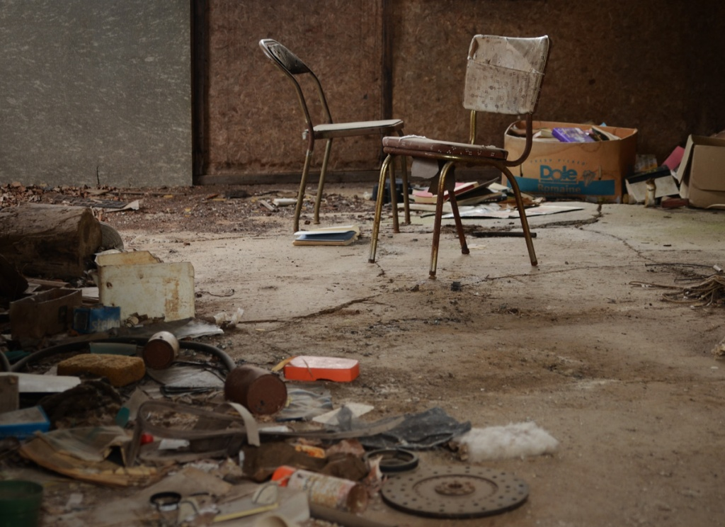 interior of old shed with two chairs, debris on the floor and boxes of books in the corner