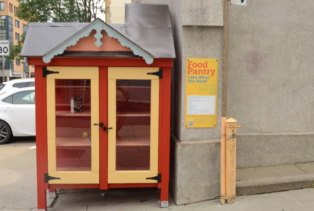 Free food pantry, shelves with glass covered doors for food to exchange, it is almost empty