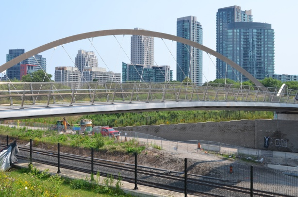 looking southeast over railway tracks, Garrison Crossing pedestrian bridge, and downtown highrises in the background
