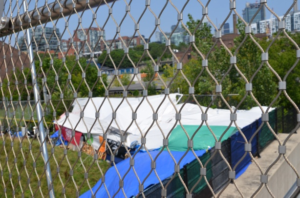 behind metal fencing on Garrison Crossing bridge, tents for homeless