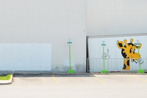 white wall back of store, truck loading zone with back of white truck and Geoffrey the Giraffe, Toys R Us symbol on the truck. Someone has graffiti black markered a smoking cigarette in his mouth