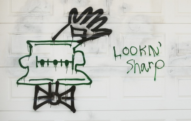 graffiti on a white garage door of a character's head with bowtie and one hand waving, words that say lookin' sharp
