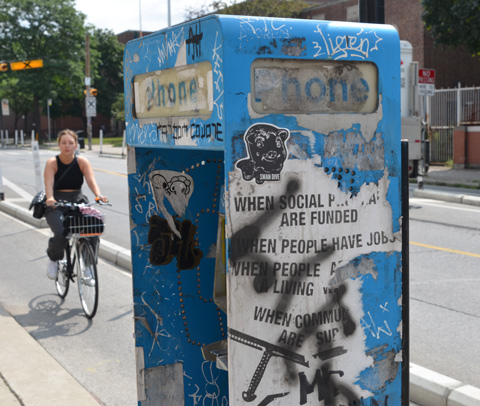 poster on a blue phone box that is torn and tagged, a woman on a bicycle is riding by