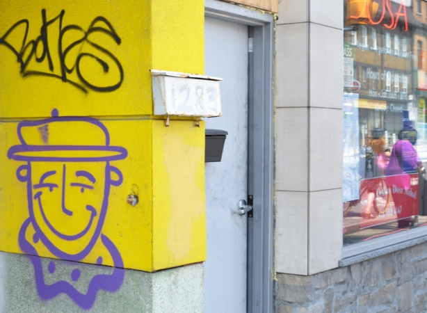 purple drawing of a man wearing a hat, on a yellow wall