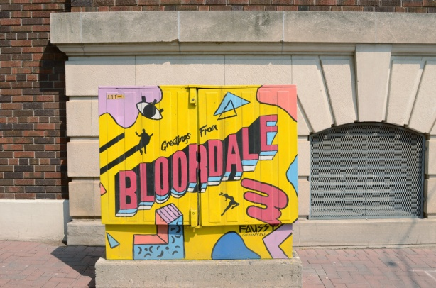 painted bell box near east entrance to Dufferin station, Greetings from Bloordale, yellow background with pink and blue images on it