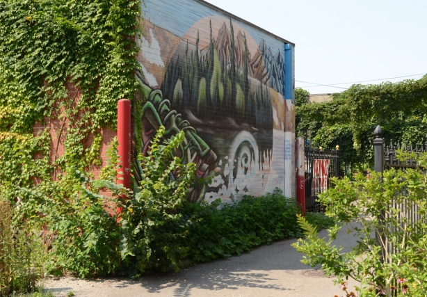 ivy on a wall of a building, a mural on the other wall, facing an alley. lake and mountains and trees in the mural
