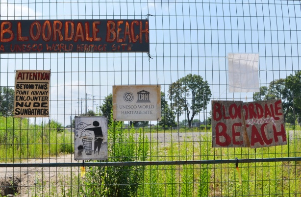 many signs on fence surrounding vacant lot including Bloordale Beach, a don't litter sign that says keep it clean, a hand drawn sign that says UNESCO world heritage site