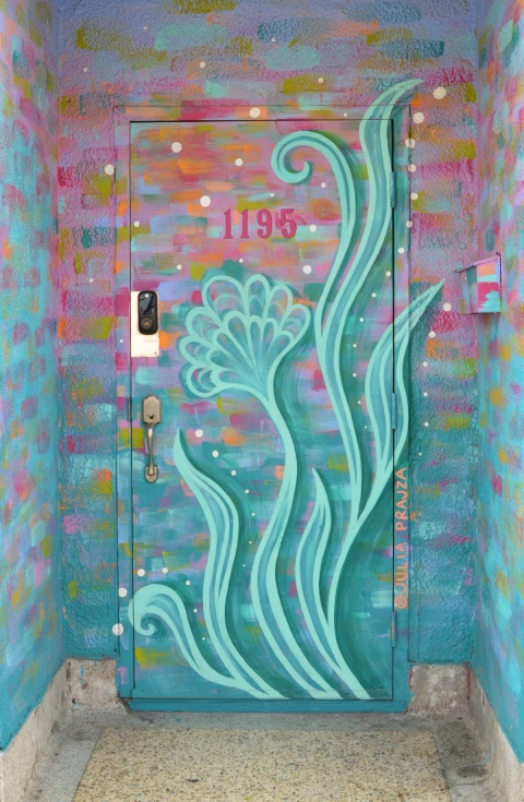 painted doorway at number 1190. Pale green leaves rising upwards on a pink and greenish blue background painted by Julia Prajza
