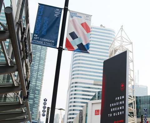 Yonge Street, looking up at banners on metal poles, tops of some highrise buildings,