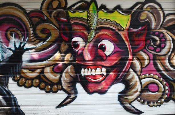 big red faced, apple?, character, street art on a garage door