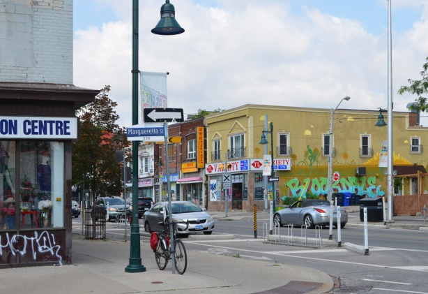 intersection of Bloor and Margueretta looking towards corner of Bloor and Emerson with Bloodale mural on the side of a building on the northwest corner
