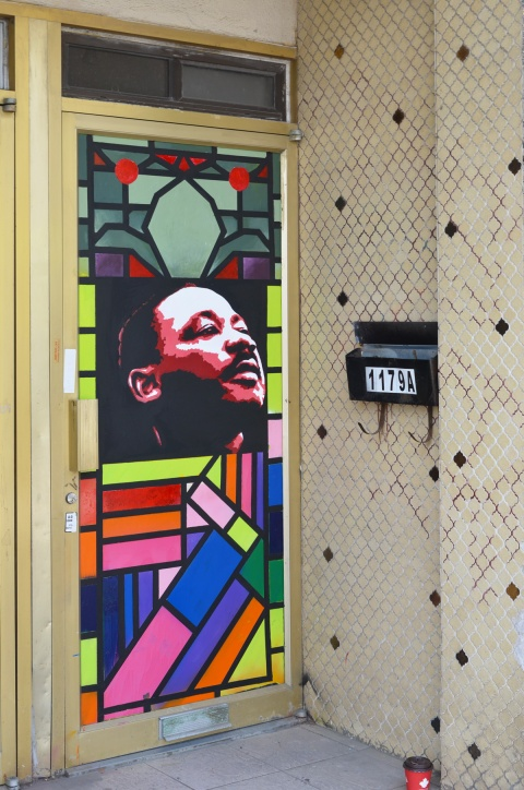 door alcove with small beige tiles, a black mailbox with number 11 on it, and an image of Martin Luther King and stained glass patterns on the door